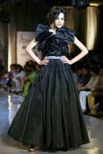 A model walks the ramp in this timeless black gown from Adarsh Gill collection.