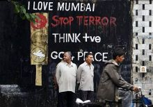 People stand in front of a graffiti put up in Mumbai