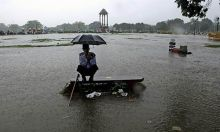 A security guard sits under an umbrella at India Gate