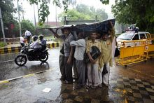 Commuters use a banner to take refuge from rain