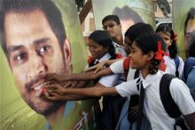 Children offer sweets to a poster of MS Dhoni on his 30th birthday