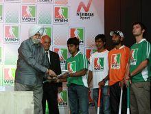 KPS Gill present a hockey stick to Arjun Hlappa