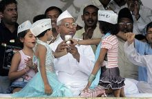 Hazare accepts a glass of coconut water from two little girls