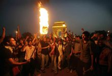 Supporters of Anna Hazare shout slogans near India Gate