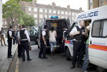 Police officers detain a woman in London