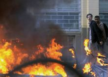 People walk behind a car burning after it was set on fire by rioters in Hackney, east London