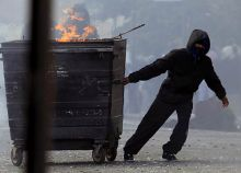 A masked youth pulls a burning garbage bin set on fire by rioters in Hackney, east London