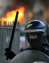 A British police officer stand guard as a car set on fire by rioters, burns in Hackney, east London