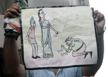 Volunteers of 'India Against Corruption' dispaly a cartoon of UPA leaders in Delhi