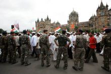 Security personnel stand guard as dabbawalas hold a rally in Mumbai