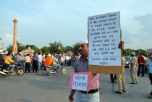 A supporter of Anna Hazare shows a placard during a protest rally in Jaipur