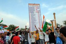 Anna Hazare supporters show a huge placard during a protest rally in Jaipur