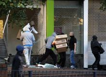 Looters take electrical goods from a shop