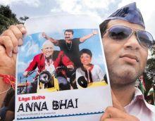 A Mumbaikar shows a poster of Anna Hazare