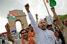 Supporters of Anna Hazare wave tricolour near India Gate