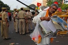 A supporters of Anna Hazare reads newspapers outside Tihar prison