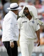 Umpire Steve Davis talks with India's Praveen