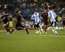 Lionel Messi goes past Venezuelan defenders