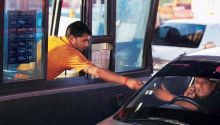 A toll plaza attendant collects toll
