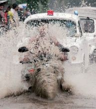 A biker gets splashed with dirty water.