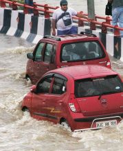 Cars wade though flodded waters in Delhi