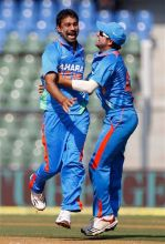 Praveen Kumar and Suresh Raina celebrate the dismissal of Craig Kieswetter
