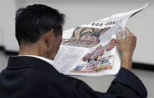 A Chinese reads a newspaper
