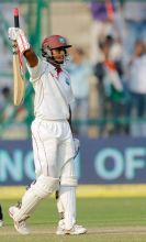 Shivnarine Chanderpaul raises his bat after scoring a century