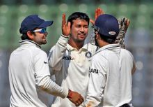 Pragyan Ojha (centre) celebrates the wicket of Kieran Powell with team-mates Virat Kohli and captain Mahendra Singh Dhoni