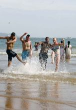 Tourists play in water at Goa beach