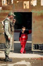 Para military soldier and a child outside polling booth