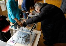 An elderly French voter casts her vote