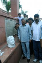 People gather around the damaged statues of former UP CM Mayawati