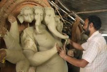 Artist prepares sand sculpture of Lord Ganesh