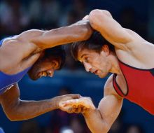 India's Yogeshwar Dutt (in blue) wrestles with Bulgaria's Anatolie llarionovitch Guidea
