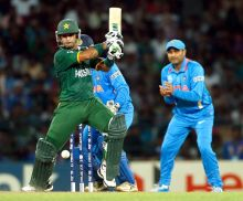 Mohammad Hafeez plays a shot, Sehwag and Dhoni in the background