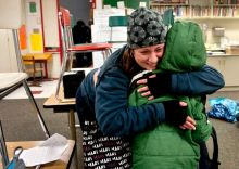 A mother tightly hugs her son After watching TV news reports of the school shooting in Connecticut.