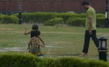 A kid is playing with his father in the soothing rains.