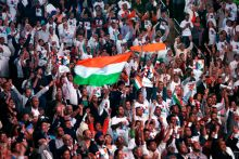 Supporters cheer and wave Indian flags