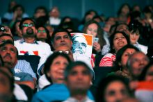 Supporters listen as Prime Minister Narendra Modi