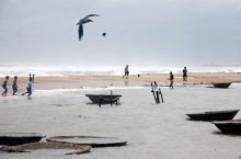 Fishermen walk along the shore at Ganjam district