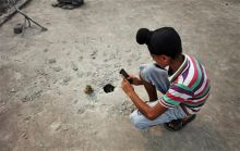 Indian boy taking photos of a mortar shell