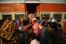 Women try to enter the ladies' compartment of a crowded train