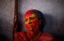 A Hindu woman is seen covered with coloured powder