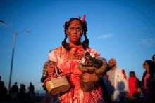 An lady takes part in the zombie walk with her fake zombie pet dog.