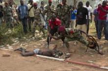Central African Army (FACA) soldier stabs the corpse of a man