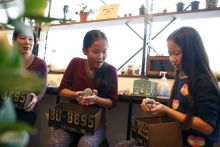 Anna (C), 11, and Yuna Cheung (R), 11, from Great Britain hold hedgehogs as their mother Kimberly Russel watches at the Harry hedgehog cafe.