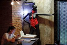 A woman uses a phone at Ke'er restaurant, where mannequins are dressed in bondage gear.