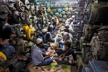 Muslims eat their Iftar (breaking of fast) meal at a water pump workshop in the old quarters of Delhi, India.