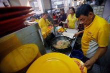 """Hawker Alex See, 66, and his daughter Penny See, 33, cooking at their Geylang Lorong 29 Fried Hokkien Mee stall at East Coast Road. """"Young people come and go, they are not serious about learning. When I was helping my father at the age of 16, I asked him"""